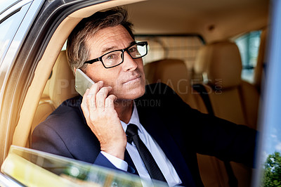 Buy stock photo Shot of a mature businessman making a phone call while sitting in the backseat of a car