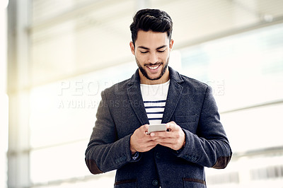 Buy stock photo Cropped shot of a handsome young businessman sending a text message while standing in his office