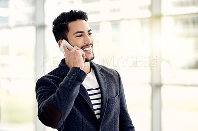Buy stock photo Cropped shot of a handsome young businessman making a phonecall while standing in his office