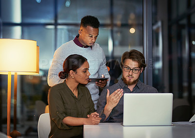 Buy stock photo Shot of a group of young businesspeople using a laptop together during a late night at work