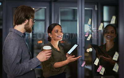 Buy stock photo Shot of a group of young businesspeople having a brainstorming session during a late night at work