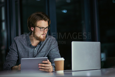 Buy stock photo Shot of a young businessman using a laptop and digital tablet during a late night at work