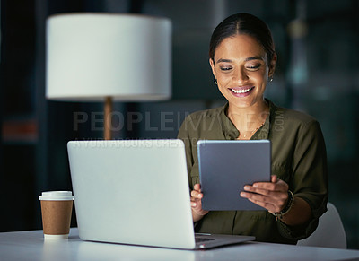 Buy stock photo Shot of a young businesswoman using a laptop and digital tablet during a late night at work