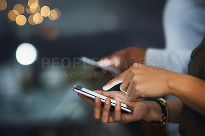 Buy stock photo Cropped shot of two unrecognizable businesspeople texting on their cellphones in the office at night