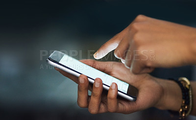 Buy stock photo Cropped shot of an unrecognizable businesswoman texting on her cellphone in the office at night