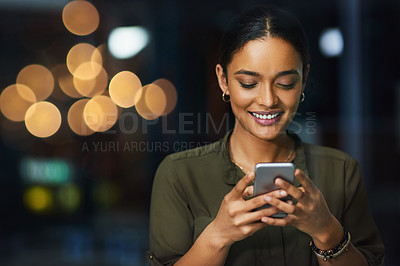 Buy stock photo Cropped shot of a cheerful young businesswoman texting on her cellphone inside the office during the night