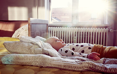 Buy stock photo Cropped shot of an adorable baby lying down on a bed at home