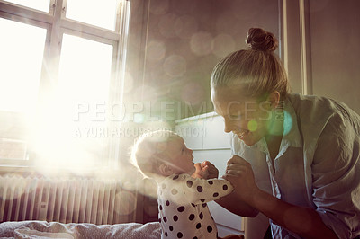 Buy stock photo Cropped shot of an affectionate young mother bonding with her baby on a bed at home