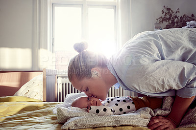 Buy stock photo Cropped shot of an affectionate young mother kissing her baby on the cheeks on a bed at home