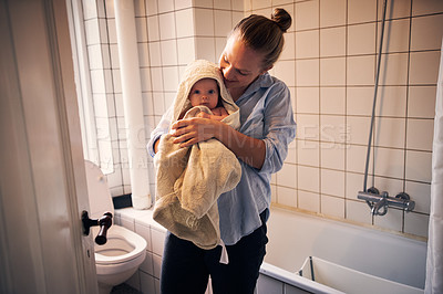 Buy stock photo Cropped shot of an affectionate young mother drying her baby with a towel after giving her a bath