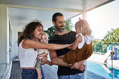 Buy stock photo Cropped shot of two loving parents being playful with their kids on their veranda at home