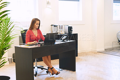 Buy stock photo Full length shot of a beautiful young businesswoman using  a laptop while sitting at her office desk at work
