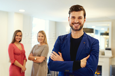 Buy stock photo Portrait of a handsome young businessman posing with his arms folded in an office with colleagues in the background