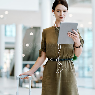 Buy stock photo Shot of a confident young businesswoman walking with her luggage while being on a video call inside of an airport