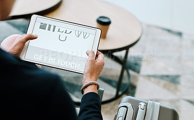 Buy stock photo Over the shoulder shot of an unrecognizable businessman browsing on a digital tablet inside of a busy airport