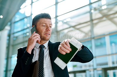 Buy stock photo Shot of a confident middle aged businessman talking on his cellphone while looking at the time on his watch inside of an airport