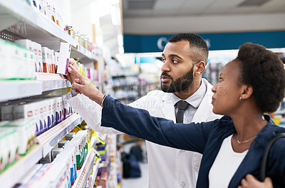 Buy stock photo Cropped shot of a confident young pharmacist helping out a pregnant woman inside of a pharmacy during the day