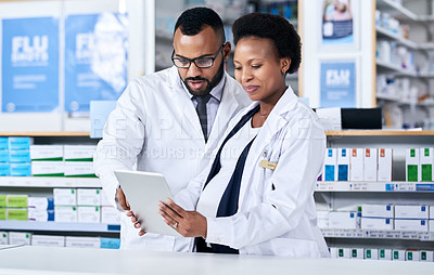 Buy stock photo Cropped shot of two cheerful young pharmacists working together on a digital tablet inside of a pharmacy during the day