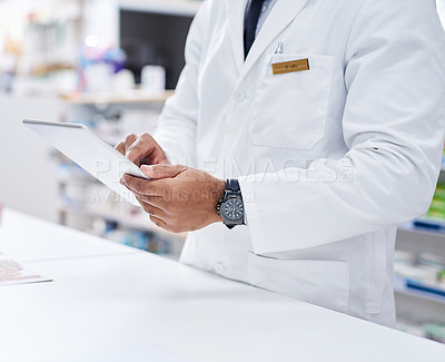 Buy stock photo Cropped shot of an unrecognizable pharmacist working on a digital tablet inside of a pharmacy during the day