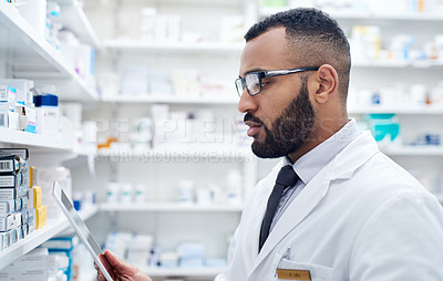 Buy stock photo Cropped shot of a confident young pharmacist working by himself inside of a pharmacy during the day