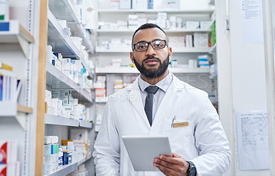 Buy stock photo Portrait of a confident young pharmacist working on a digital tablet inside of a pharmacy during the day