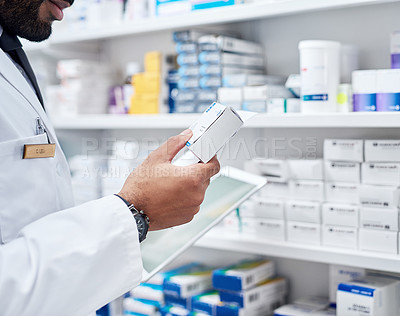 Buy stock photo Cropped shot of a unrecognizable pharmacist working by himself inside of a pharmacy during the day