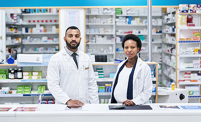 Buy stock photo Portrait of two pharmacists working behind the counter in a chemist