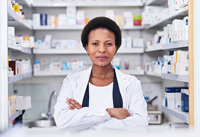 Buy stock photo Portrait of a young pharmacist standing with her arms crossed in a chemist