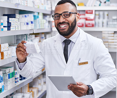 Buy stock photo Portrait of a young pharmacist working on a digital tablet while checking stock in a chemist