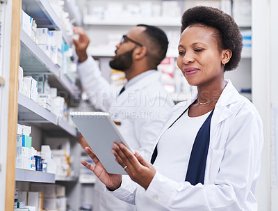 Buy stock photo Shot of a pharmacist using a digital tablet while working with her colleague in a chemist