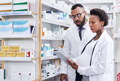 Buy stock photo Shot of two pharmacists using a digital tablet while checking stock in a chemist
