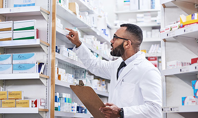 Buy stock photo Shot of a young pharmacist holding a clipboard while checking stock in a chemist