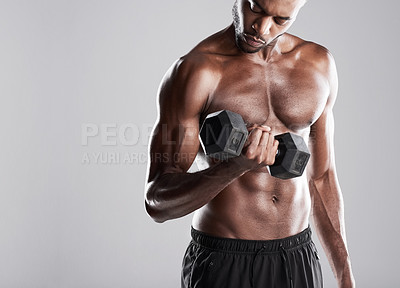 Buy stock photo Studio shot of a muscular young man lifting weights while standing against a grey background