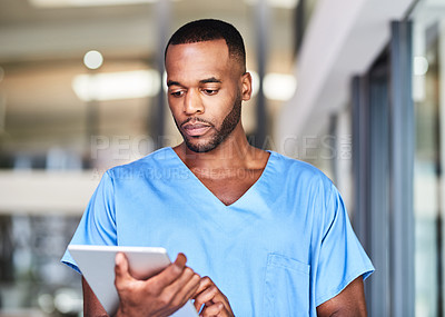 Buy stock photo Shot of a young medical practitioner using a digital tablet in a hospital