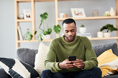 Buy stock photo Cropped shot of a handsome young man using his cellphone while chilling on the sofa at home