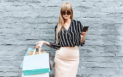 Buy stock photo Shot of a beautiful and stylish young woman using a smartphone while shopping in the city