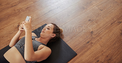 Buy stock photo Shot of a sporty young woman using a cellphone while practicing yoga in a studio