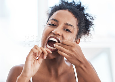 Buy stock photo Portrait of a beautiful young woman flossing her teeth in the bathroom at home