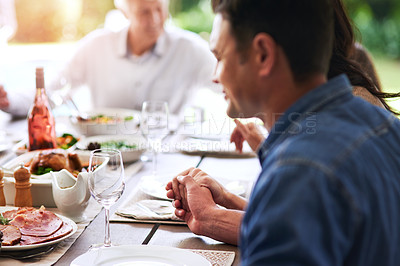 Buy stock photo Cropped shot of an unrecognizable young man holding hands with his family to say grace while dining outdoors