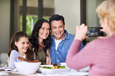 Buy stock photo Cropped shot of a  grandmother taking a photo of her family during lunch indoors