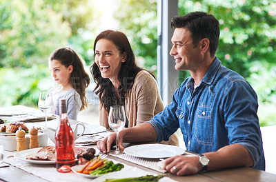 Buy stock photo Cropped shot of a happy young woman laughing happily during lunch with her family outdoors