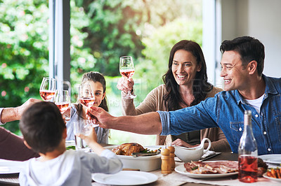 Buy stock photo Cropped shot of a cheerful family making a toast while enjoying lunch at home