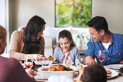 Buy stock photo Cropped shot of an affectionate mother serving her family during lunch at home