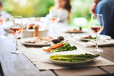 Buy stock photo Cropped shot of a dining table set with food and drink with a group of people in the background