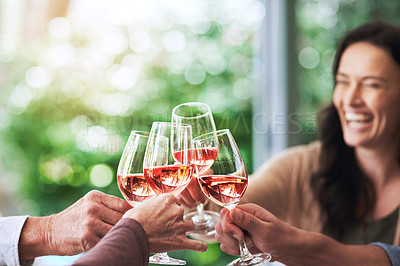 Buy stock photo Cropped shot of an attractive young woman having a celebratory toast with her family outdoors
