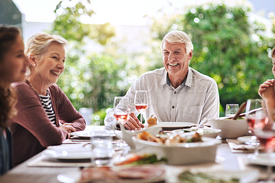 Buy stock photo Cropped shot of an affectionate aged man dining with his family for lunch outdoors