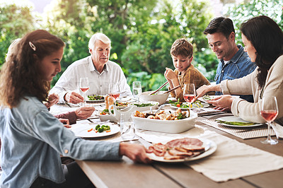 Buy stock photo Cropped shot of an affectionate young woman serving her family during lunch outdoors