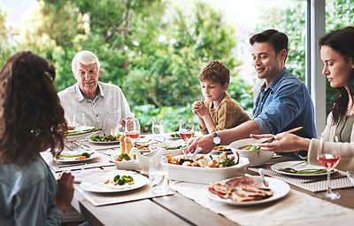Buy stock photo Cropped shot of an affectionate young man enjoying lunch with his family outdoors