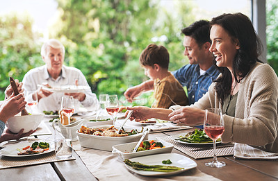 Buy stock photo Cropped shot of a happy young woman enjoying lunch with her family outdoors