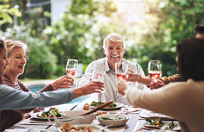 Buy stock photo Cropped shot of a happy aged man making a toast with his family during lunch outdoors